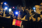 Demonstrators hold up the mobile phone lights as they form human chain at the Peak, tourist spot in Hong Kong, Friday, Sept. 13, 2019. Protest-related activities are expected to continue Friday, when Chinese celebrate the Mid-Autumn Festival with lanterns and mooncakes. Police banned a planned major march in central Hong Kong on Sunday, but many protesters have said they will turn up anyway. (AP Photo/Kin Cheung)