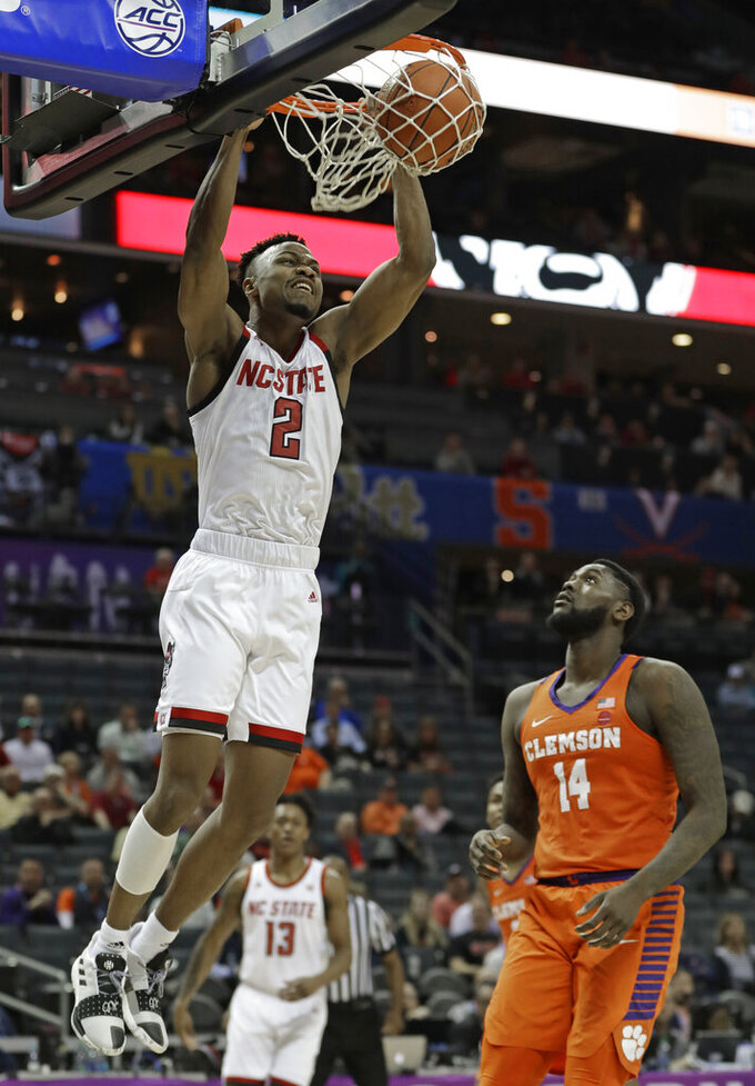 North Carolina State's Torin Dorn (2) dunks past Clemson's Elijah Thomas (14) during the first half of an NCAA college basketball game in the Atlantic Coast Conference tournament in Charlotte, N.C., Wednesday, March 13, 2019. (AP Photo/Nell Redmond)