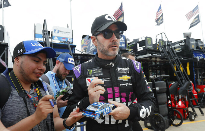 Jimmie Johnson looks up while signing autographs before practice for the NASCAR Cup Series auto race at Texas Motor Speedway in Fort Worth, Texas, Friday, March 29, 2019. (AP Photo/LM Otero)
