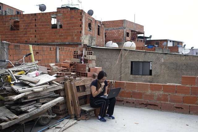 Maria Figueroa, a 34-year-old mother of four, fails to connect to the internet to send pictures of her sons' homework back to their teachers, from the roof of her apartment, which has gone two weeks without running water in the Catia neighborhood of Caracas, Venezuela, Wednesday, May 6, 2020. With schools shut down amid the new coronavirus pandemic, students with connectivity receive online instruction, but most are not connected, nor have devices, requiring parents and teachers to make trips to schools. (AP Photo/Ariana Cubillos)