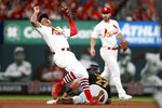 St. Louis Cardinals second baseman Kolten Wong, left, spins away after tagging out Pittsburgh Pirates' Kevin Newman (27) on a failed stolen base attempt during the fifth inning of a baseball game Tuesday, July 16, 2019, in St. Louis. Watching in the background is Cardinals shortstop Paul DeJong, right. (AP Photo/Jeff Roberson)