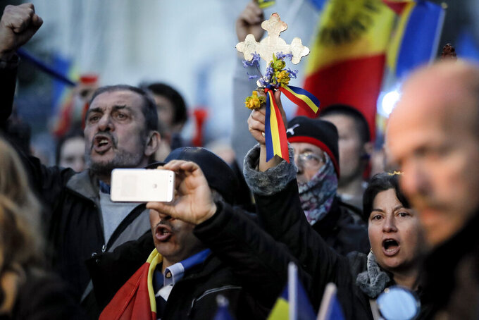 People protest outside the Cotroceni Presidential Palace in Bucharest, Romania, Saturday, April 10, 2021. Marchers took to the streets Saturday in the Romanian capital of Bucharest to protest restrictive measures to fight the spread of COVID-19 even as new daily infections and deaths rose in the European Union nation. (AP Photo/Vadim Ghirda)