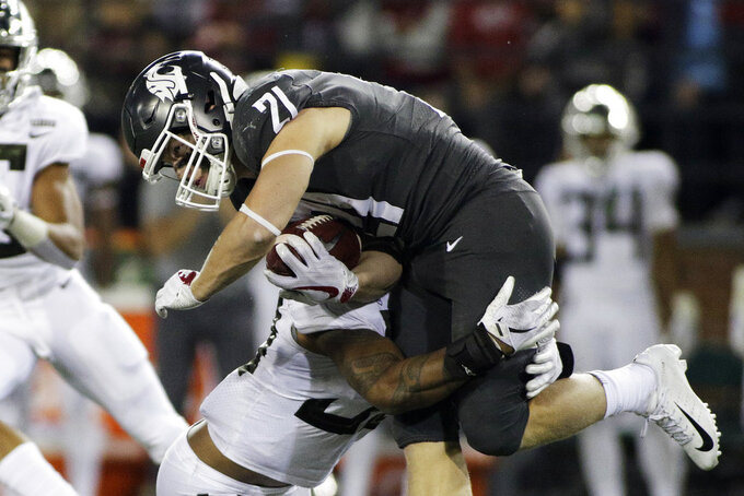 Oregon linebacker Kaulana Apelu, left, tackles Washington State running back Max Borghi (21) during the second half of an NCAA college football game in Pullman, Wash., Saturday, Oct. 20, 2018. Washington State won 34-20. (AP Photo/Young Kwak)