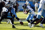 Tennessee Titans running back Dion Lewis (33) fumbles during the first half of an NFL football game while Carolina Panthers cornerback Donte Jackson (26) looks to recover the ball in Charlotte, N.C., Sunday, Nov. 3, 2019. (AP Photo/Brian Blanco)