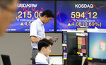 A currency trader uses a calculator as another watches a monitor at the foreign exchange dealing room of the KEB Hana Bank headquarters in Seoul, South Korea, Monday, Aug. 12, 2019. Asian stocks gained Monday amid investor jitters the U.S.-China trade war might be worsening. (AP Photo/Ahn Young-joon)