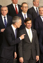 U.S. Secretary for Defense Mark Esper, front right, speaks with NATO Secretary General Jens Stoltenberg, front left, during a group photo of NATO defense ministers at NATO headquarters in Brussels, Wednesday, Feb. 12, 2020. NATO ministers, in a two-day meeting will discuss building stability in the Middle East, the Alliance's support for Afghanistan and challenges posed by Russia's missile systems. (AP Photo/Virginia Mayo)