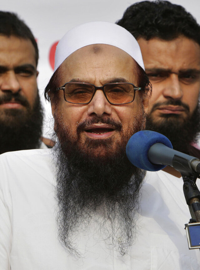 FILE - In this Oct. 26, 2018 file photo, Hafiz Saeed, founder of Pakistani religious group Jamaat-ud-Dawa addresses an anti-Indian rally in Lahore, Pakistan. On Wednesday, Feb. 12, 2020, a Pakistani court sentenced Saeed, a radical cleric wanted by Washington and New Delhi for his  role in the 2008 Mumbai attacks, and four of his associates to five and half years each in jail on terror financing. According to a government and defense lawyer, Wednesday's verdict was announced in the presence of Hafiz Saeed and the four other suspects. (AP Photo/K.M. Chaudary, File)