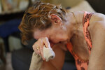 Sandra Sheffield, 72, reacts to her predicament, as she uses a washcloth to wipe sweat from her face, in her home, which now has no electricity, in the aftermath of Hurricane Michael in Panama City, Fla., Wednesday, Oct. 17, 2018. She and her husband refuse to leave their home, and neighbors are trying to assist them with fans and a generator. (AP Photo/Gerald Herbert)