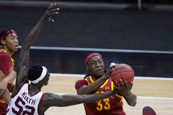 Iowa State forward Solomon Young (33) pulls in a rebound next to Oklahoma forward Kur Kuath (52) during the first half of an NCAA college basketball game in the first round of the Big 12 men's tournament in Kansas City, Mo., Wednesday, March 10, 2021. (AP Photo/Orlin Wagner)