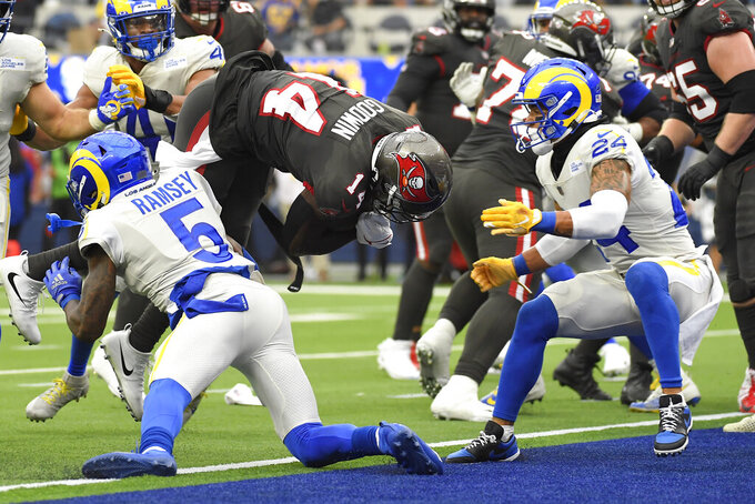 Tampa Bay Buccaneers wide receiver Chris Godwin, top center, scores a touchdown over Los Angeles Rams cornerback Jalen Ramsey (5) during the first half of an NFL football game Sunday, Sept. 26, 2021, in Inglewood, Calif. (AP Photo/Kevork Djansezian)