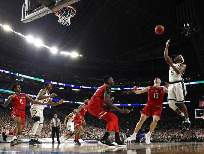 Michigan State guard Cassius Winston (5) shoots over Texas Tech guard Matt Mooney (13) during the first half in the semifinals of the Final Four NCAA college basketball tournament, Saturday, April 6, 2019, in Minneapolis. (AP Photo/David J. Phillip)
