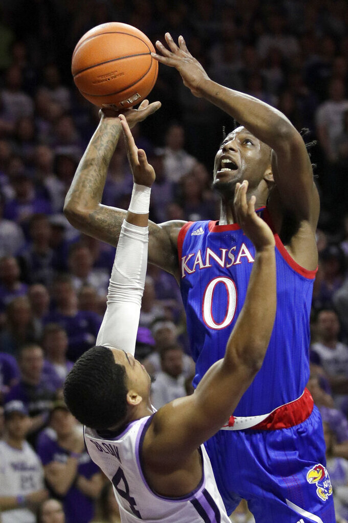 FILE - Kansas guard Marcus Garrett (0) shoots over Kansas State guard David Sloan (4) during the first half of an NCAA college basketball game in Manhattan, Kan., in this Saturday, Feb. 29, 2020, file photo. The Jayhawks will be challenged enough in the Big 12, where a double round-robin means two games each against second-ranked Baylor, No. 14 Texas Tech, No. 15 West Virginia and No. 19 Texas. (AP Photo/Orlin Wagner, File)