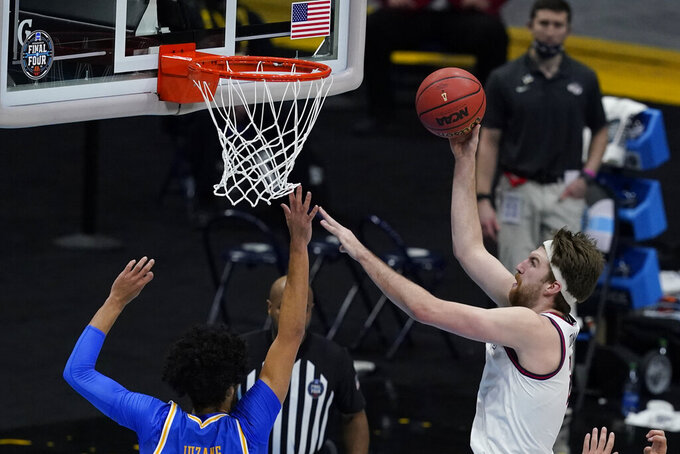 Gonzaga forward Drew Timme, right, drives to the basket over UCLA guard Johnny Juzang, left, during the second half of a men's Final Four NCAA college basketball tournament semifinal game, Saturday, April 3, 2021, at Lucas Oil Stadium in Indianapolis. (AP Photo/Darron Cummings)