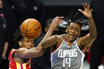 Atlanta Hawks forward De'Andre Hunter and Los Angeles Clippers guard Terance Mann go after a rebound during the first half of an NBA basketball game Monday, March 22, 2021, in Los Angeles. (AP Photo/Mark J. Terrill)