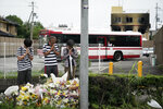 People pay their respects at a makeshift memorial to honor the victims of Thursday's fire at the Kyoto Animation Studio building, background right, Saturday, July 20, 2019, in Kyoto, Japan. The man suspected of setting ablaze a beloved Japanese animation studio was raging about theft and witnesses and media reported he had a grudge against the company, as questions arose why such mass killings keep happening in the country. (AP Photo/Jae C. Hong)