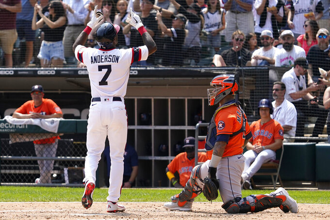 Chicago White Sox's Tim Anderson, left, celebrates after hitting a solo home run, next to Houston Astros catcher Martin Maldonado during the fifth inning of a baseball game in Chicago, Sunday, July 18, 2021. (AP Photo/Nam Y. Huh)