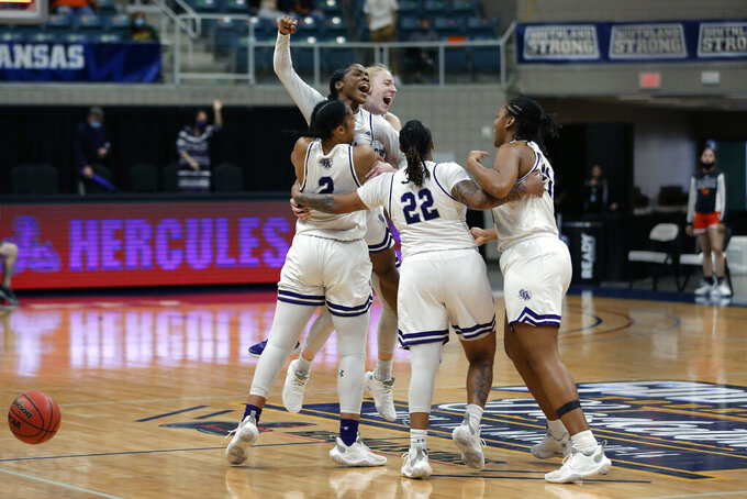 Stephen F. Austin players celebrate on the court after the final buzzer of their win over Sam Houston State after an NCAA college basketball game for the Southland Conference women's tournament championship Sunday, March 14, 2021, in Katy, Texas. (AP Photo/Michael Wyke)