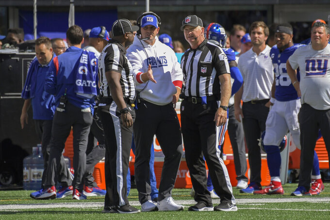 New York Giants head coach Joe Judge, center, speaks with referees on the sidelines during the first half of an NFL football game against the Atlanta Falcons, Sunday, Sept. 26, 2021, in East Rutherford, N.J. (AP Photo/Bill Kostroun)