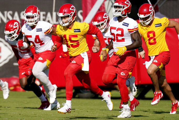Kansas City Chiefs quarterback Patrick Mahomes (15) runs with teammates during an NFL football training camp practice Monday, Aug. 17, 2020, in Kansas City, Mo. (AP Photo/Charlie Riedel)