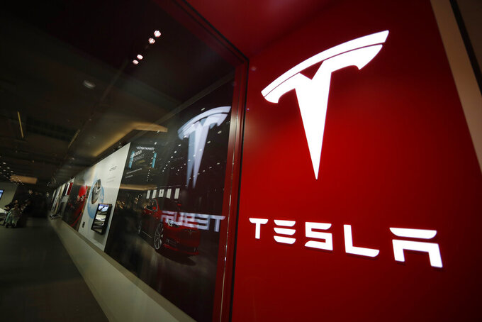 FILE - This Feb. 9, 2019, file photo shows a sign bearing the company logo outside a Tesla store in Cherry Creek Mall in Denver. Federal safety regulators have sent a team to investigate the fatal crash of a Tesla electric car near Houston in which local authorities say no one was behind the wheel.T he National Highway Traffic Safety Administration said Monday, April 19, 2021, it has sent a Special Crash Investigation team to Spring, Texas, to look into the fiery Saturday night, April 17 crash that killed two men. (AP Photo/David Zalubowski, File)