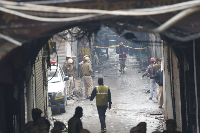 Police officers cordon off the site of a fire in a narrow lane in New Delhi, India, Sunday, Dec. 8, 2019. A doctor at a government-run hospital says dozens have died in a major fire in central New Delhi. (AP Photo/Manish Swarup)