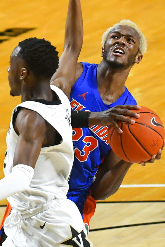Florida guard Scottie Lewis (23) looks to the basket as Vanderbilt guard Trey Thomas defends during the second half of an NCAA college basketball game Wednesday, Dec. 30, 2020, in Nashville, Tenn. (AP Photo/John Amis)