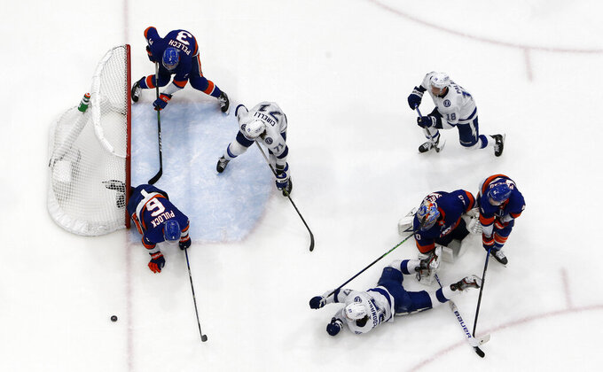 New York Islanders defenseman Ryan Pulock (6) clears the puck from the crease during the final seconds of after a shot from Tampa Bay Lightning defenseman Ryan McDonagh (27) during the third period in Game 4 of an NHL hockey Stanley Cup semifinal, Saturday, June 19, 2021, in Uniondale, N.Y. (AP Photo/Jim McIsaac)