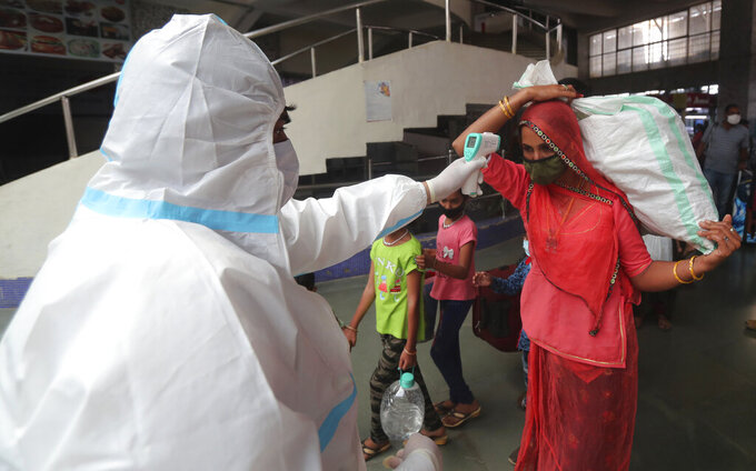 A health worker checks the temperature of a passenger at Bandra train station in Mumbai, India, Wednesday, Feb. 17, 2021. Health officials have detected a spike in COVID-19 cases in several pockets of Maharashtra state, including in Mumbai, the country's financial capital. (AP Photo/Rafiq Maqbool)