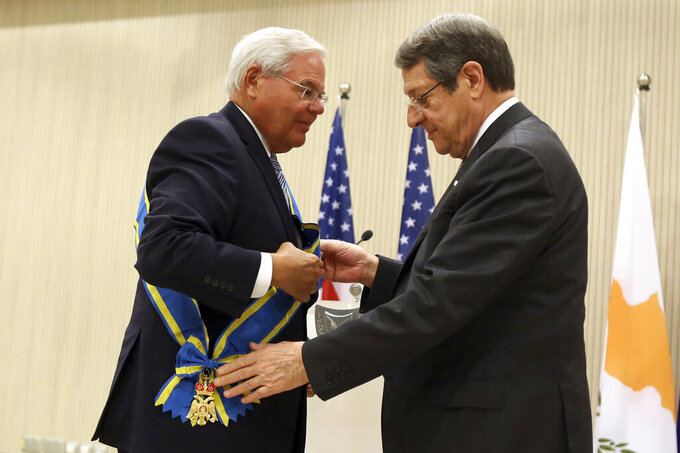"""U.S. Senate Foreign Relations Committee Chairman Robert Menendez, left, receives Cyprus' highest honor - the Grand Collar of the Order of Makarios III - from President Nicos Anastasiades during a ceremony at the Presidential Palace in the capital Nicosia, Monday, Aug. 30, 2021. Menendez, the Democratic senator from New Jersey said that the """"retrograde vision"""" of Turkey's president to cement Cyprus' ethnic divide by striving for a two-state deal """"is wrong"""" for all Cypriots. (AP Photo/Philippos Christou)"""