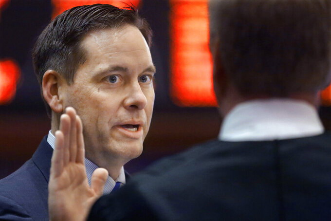 FILE - In this Tuesday, March 3, 2015 file photo, Illinois Rep. Tim Butler, R-Springfield, takes the oath of office in the House chambers at the Illinois State Capitol in Springfield, Ill. Butler joined three other GOP lawmakers Thursday, Oct. 29, 2020 in objecting to Democratic Gov. J.B. Pritzker's imposition of restrictions on indoor dining and drinking in central Illinois, the ninth of 11 COVID-19 monitoring regions to see such restrictions this month because of troubling coronavirus numbers. Butler, who tested positive for COVID-19 last weekend and is quarantining at home, said while Pritzker's intentions are good, his focus on the health side of the pandemic has come at the expense of the economic damage it has wrought. (AP Photo/Seth Perlman, File)