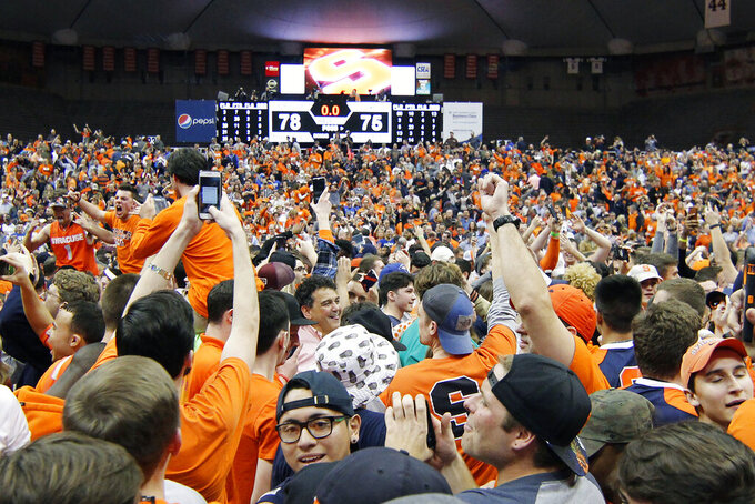 FILE - In this Feb. 22, 2017, file photo, Syracuse fans celebrate on the court after beating Duke in an NCAA college basketball game in Syracuse, N.Y. The virus that causes COVID-19 is most easily spread when an infected person coughs, sneezes or talks, allowing droplets to land in the mouths or noses of people nearby. That's why most recent guidelines from the Centers for Disease Control continue to preach 6 feet of separation in public setting as among the most important ways to stop the spread. (AP Photo/Nick Lisi, File)