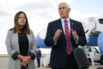Vice President Mike Pence speaks to members of the media at Andrews Air Force Base, Md., Monday, Oct. 5, 2020, as he leaves Washington for Utah ahead of the vice presidential debate schedule for Oct. 7. At left is Karen Pence. (AP Photo/Jacquelyn Martin)