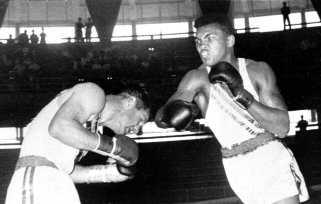 FILE - In this Sept. 3, 1960, file photo, Cassius Clay, 18-year-old from Louisville, Ky., throws a right at Tony Madigan of Australia, left, during the light heavyweight boxing semi-finals at the Summer Olympic Games in Rome. The 1960 Rome Summer Olympics set the standard for every Olympiad to follow. These Games were the first televised in the United States (AP Photo/File)
