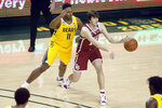 Oklahoma guard Austin Reaves, right, passes the ball as Baylor guard Mark Vital, left defends during the first half of an NCAA college basketball game on Wednesday, Jan. 6, 2021, in Waco, Texas. (AP Photo/Ray Carlin)