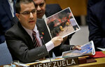 FILE - In this Feb. 26, 2019 file photo, Venezuela Foreign Affairs Minister Jorge Arreaza shows pictures he said represent opposition members initiating violence, during a meeting on Venezuela in the U.N. Security Council at U.N. headquarters. Arreaza has accused the United States of violating articles of the Vienna Convention on Diplomatic Relations that require host countries to protect foreign embassy buildings even when ties are severed. (AP Photo/Bebeto Matthews, File)