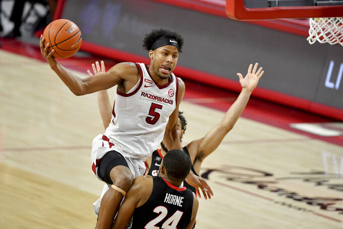 Arkansas guard Moses Moody (5) drives to the hoop against Georgia defender P.J. Horne (24) during the second half of an NCAA college basketball game Saturday, Jan. 9, 2021, in Fayetteville, Ark. (AP Photo/Michael Woods)