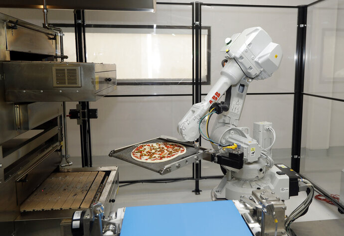 FILE - In this Aug. 29, 2016, file photo, a robot places a pizza into an oven at Zume Pizza in Mountain View, Calif. It has not been a good week for robots in the San Francisco Bay Area. A Silicon Valley company that used robots to make its pizzas closed this week and three coffee shops in downtown San Francisco that used robots as baristas also shuttered. Zume Pizza said it is cutting 172 jobs in Mountain View, and eliminating another 80 jobs at its facility in San Francisco. Zume Chief Executive Alex Garden made the announcement about Zume in an email to company employees on Wednesday, Jan. 8, 2020, the Mercury News reported. (AP Photo/Marcio Jose Sanchez, File)