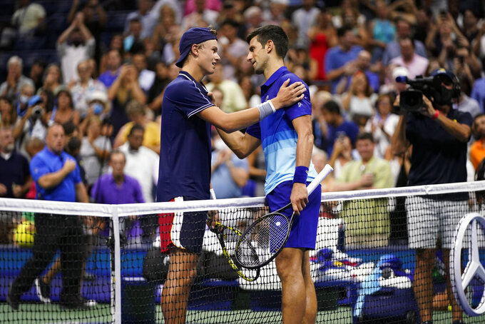 Holger Vitus Nodskov Rune of Denmark, left, and Novak Djokovic, of Serbia, meet at the net after Djokovic won their first-round match at the US Open tennis championships, Tuesday, Aug. 31, 2021, in New York. (AP Photo/Frank Franklin II)