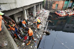 Workers collect trash during a clean-up after flood in Jakarta, Indonesia, Sunday, Jan. 5, 2020. Landslides and floods triggered by torrential downpours have left dozens of people dead in and around Indonesia's capital, as rescuers struggled to search for people apparently buried under tons of mud, officials said Saturday. (AP Photo/Tatan Syuflana)