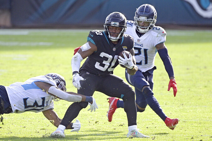 Jacksonville Jaguars running back James Robinson (30) tires to get around Tennessee Titans safety Kevin Byard, left, and cornerback Malcolm Butler (21) during the second half of an NFL football game, Sunday, Dec. 13, 2020, in Jacksonville, Fla. (AP Photo/Phelan M. Ebenhack)