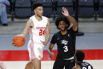 Houston guard Quentin Grimes (24) passes the ball around Central Florida forward Isaiah Adams (3) who defends during the first half of an NCAA college basketball game Sunday, Jan. 17, 2021, in Houston. (AP Photo/Michael Wyke)