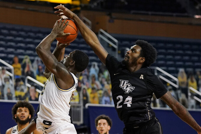Central Florida guard Dre Fuller Jr. (24) attempts to block a shot by Michigan guard Chaundee Brown during the second half of an NCAA college basketball game, Sunday, Dec. 6, 2020, in Ann Arbor, Mich. (AP Photo/Carlos Osorio)