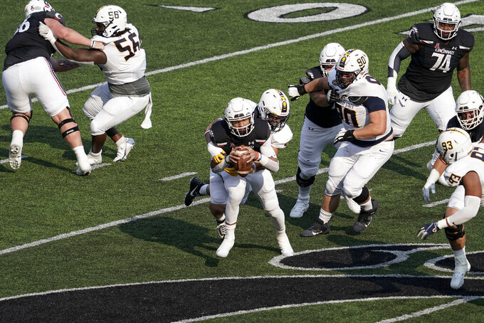 Cincinnati quarterback Desmond Ridder, front center, is sacked by Murray State linebacker Scotty Humpich during the second half of an NCAA college football game Saturday, Sept. 11, 2021, in Cincinnati. (AP Photo/Jeff Dean)