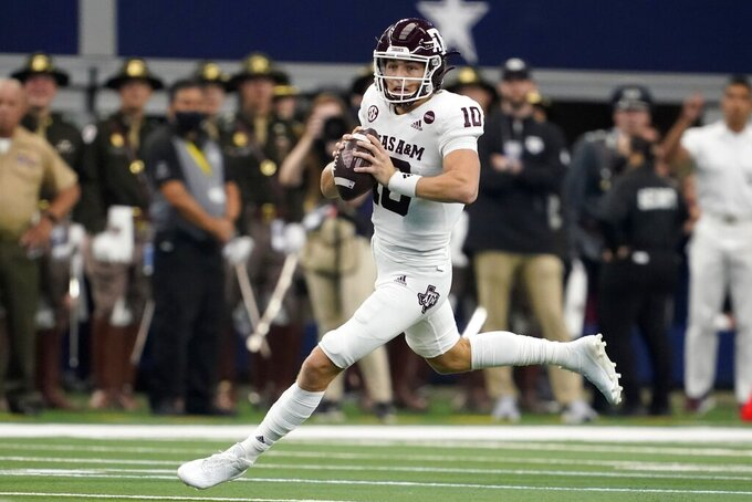 Texas A&M quarterback Zach Calzada scrambles out of the pocket before throwing a pass in the first half of an NCAA college football game in Arlington, Texas, Saturday, Sept. 25, 2021. (AP Photo/Tony Gutierrez)
