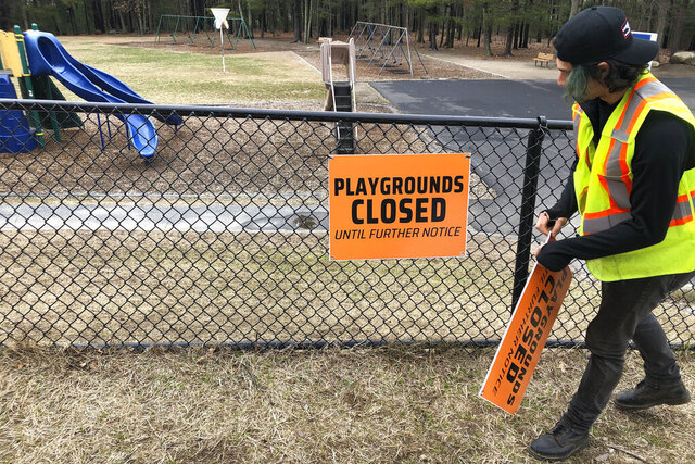 A Department of Public Works worker places a closed sign near an entrance to a playground at an elementary school, in Walpole, Mass., Friday, March 20, 2020, out of concern about the spread of the coronavirus. For most people, the new coronavirus causes only mild or moderate symptoms, such as fever and cough. For some, especially older adults and people with existing health problems, it can cause more severe illness, including pneumonia. The vast majority of people recover from the new virus. (AP Photo/Steven Senne)