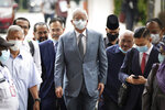 Former Malaysian Prime Minister Najib Razak, center, wearing a face mask walks toward court house in Kuala Lumpur, Malaysia, Thursday, June 4, 2020. Closing arguments are expected in the first corruption trial of him linked to the multibillion-dollar looting of the 1MDB state investment fund. (AP Photo/Vincent Thian)