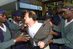 FILE - In this May 16, 2003, file photo, journalist Andrew Meldrum is manhandled by police and pushed into a car after being issued with a