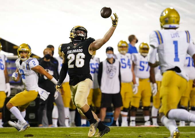 Colorado linebacker Carson Wells, center, inercept a pass thrown by UCLA quarterback Dorian Thompson-Robinson, right, for wide receiver Kyle Philips, left, in the first half of an NCAA college football game Saturday, Nov. 7, 2020, in Boulder, Colo. (AP Photo/David Zalubowski)