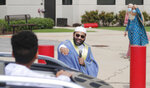 Sheikh Yasir Qadhi, center, speaks to a passing child during an Eid al-Fitr drive through celebration outside a closed mosque in Plano, Texas, Sunday, May 24, 2020. Many Muslims in America are navigating balancing religious and social rituals with concerns over the virus as they look for ways to capture the Eid spirit this weekend. (AP Photo/LM Otero)