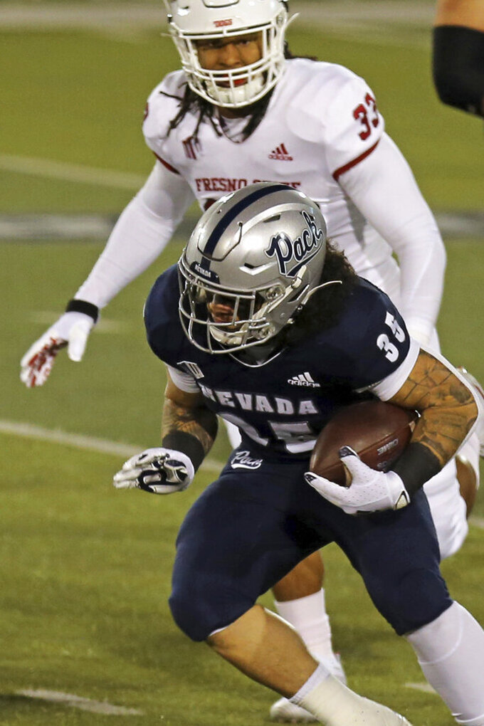 Nevada's Toa Taua (35) runs for a first down against Fresno State during the first half of an NCAA college football game Saturday, Dec. 5, 2020, in Reno, Nev. (AP Photo/Lance Iversen)